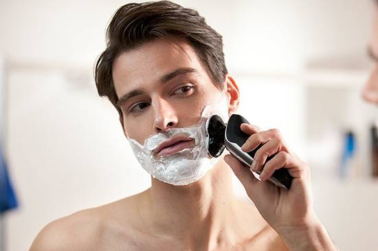Man shaving with Philips Norelco 9300 electric shaver